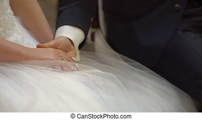 Closeup of Bride and Groom Holding Hands Sitting