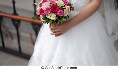 closeup of bride hands holding beautiful bouquet