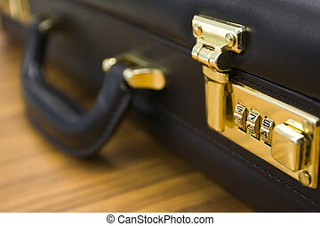 A closeup shot of a brief case, with the combination lock in focus.