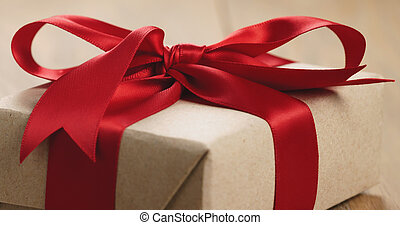 Closeup of brown paper gift box with red ribbon bow on oak table