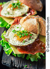 Closeup of burger with lettuce, bacon and eggs