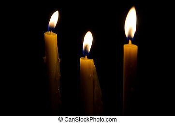 Closeup of burning candle isolated on black background.