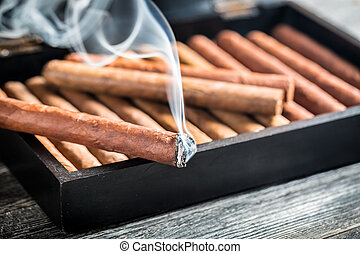 Closeup of burning cigar on wooden humidor