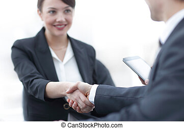 closeup of business woman shaking hands with her...