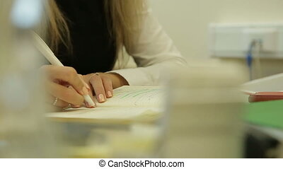 Closeup of business woman writes a pen in daily, wooden table