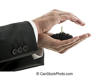 Closeup of businessman holding a pinch of fertile soil with green sprout