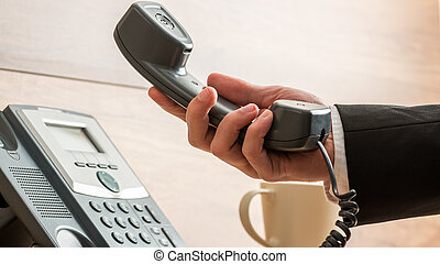 Closeup of businessman holding handset of a black landline telephone