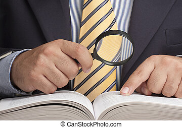 Closeup of businessman holding magnifying glass and looking for information