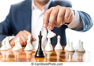 Closeup of businessman playing chess and beating black king...