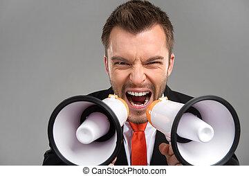 Closeup of businessman screaming in two megaphones isolated on grey background. Businessman speaking loud through megaphones