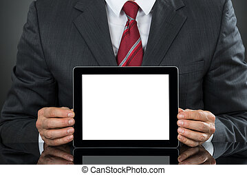 Businessman Showing Tablet With Blank Screen At Desk