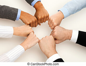 closeup of businesspeople hands in fists in circle -...