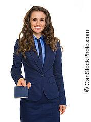 Closeup of businesswoman in suit handing over blue passport...