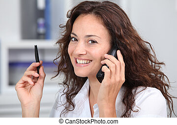Closeup of businesswoman in the office talking on the phone