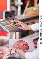 Closeup of butcher holding cold cuts while pressing button ...