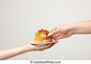Closeup female hands and cake with fresh fruits isolated on gray background.