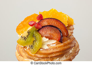 Closeup of cake with fresh fruits isolated on gray background.