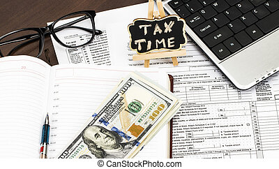 Closeup of calculator,  tax forms with the glasses, money and the pen and TAX TIME written on chalkboard