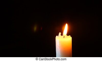 closeup of candle on black. Dying out the flame of a white candle. Smoke from the wick. 4 k. Slow-motion shooting