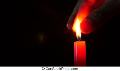 closeup of candle on black. Someone extinguishes the flame...