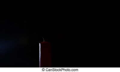 closeup of candle on black. Someone lights a candle with a...