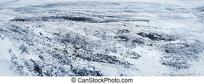 Closeup of car tire tracks in winter on the road