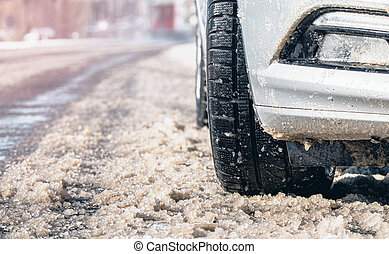 Closeup of car tires in winter on the road covered with snow. Selective focus