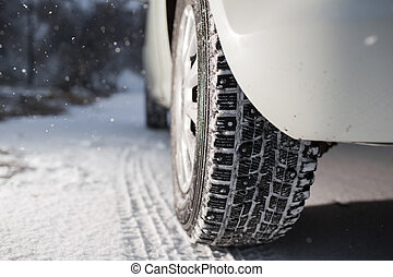Closeup of car tires in winter. the first snow in late autumn