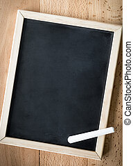 Closeup of chalk lying on blackboard over wooden background