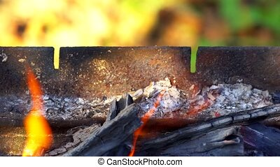 Closeup of charcoal burning under a barbecue grill burn fire...