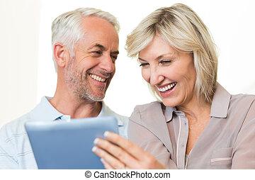Closeup of cheerful mature couple using digital tablet -...