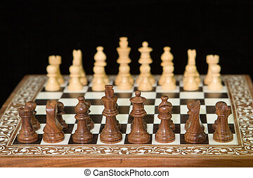 closeup of chess pieces on a wooden chess board