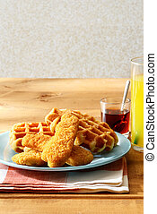 chicken tenders with waffles and a glass of orange juice
