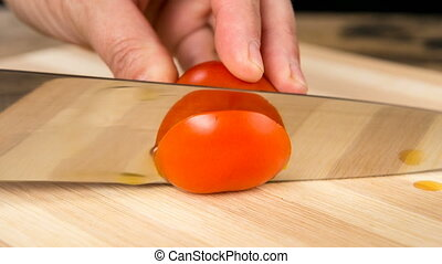Closeup of chopping tomato on wooden cutting board