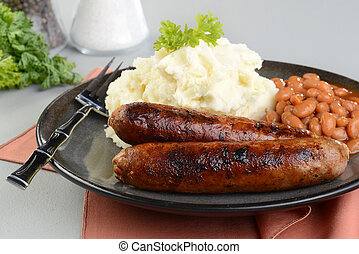 closeup of chorizo sausages with mashed potato and baked beans