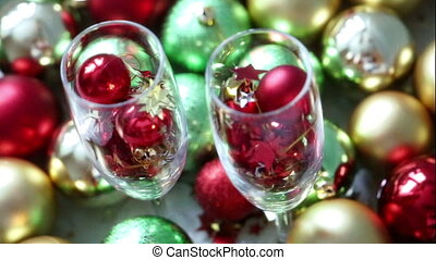Christmas balls and confetti in wineglass on a bright abstract background