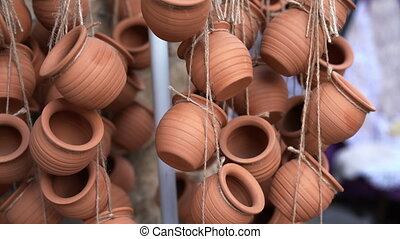Closeup of clay ceramic pots hanging on ropes and fluttering...
