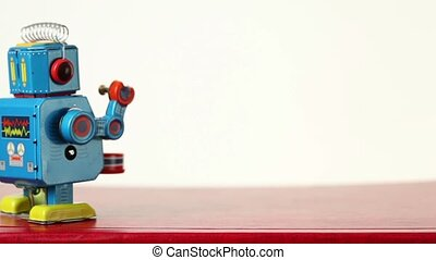 Closeup of clockwork robot walks on table, beats drum -...