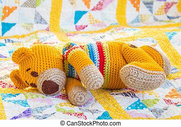 colourful crochet teddy bear left lying on quilt cover