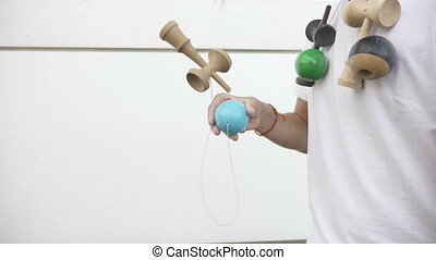 Closeup of confident boy playing with kendama toy and...