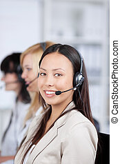 Closeup of confident customer service executive using headphones with coworkers in background at office