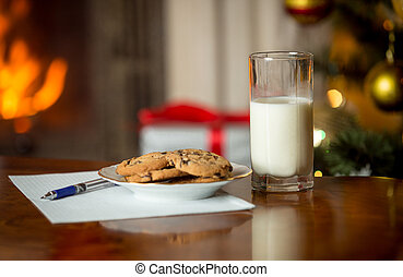 Closeup of cookies, glass of milk and letter for Santa Claus on table next to burning fireplace and Christmas tree