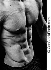 Closeup of cool perfect sexy strong sensual bare torso with abs pectorals 6 pack muscles chest black and white studio, vertical picture