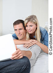 Closeup of couple sitting in sofa surfing on internet