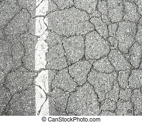 closeup of cracked asphalt road