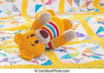 crochet teddy bear lying on quilt cover