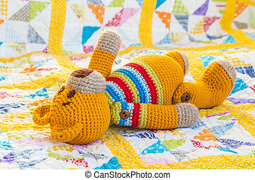crochet teddy bear on colourful quilt cover with copy space