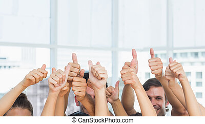 Closeup of cropped people gesturing thumbs up in a bright...