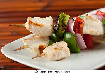 closeup of cubed chicken kabobs with red peppers, green peppers and red onion plate