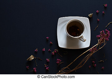 Closeup of cup of tea on dark blue background with flowers.